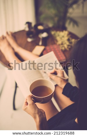 Woman with big mug of tea reading a book and making notes - stock photo