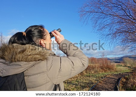 woman with binoculars birdwatching, looking up at tree - stock photo