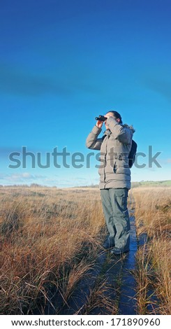 woman with binoculars birdwatching, standing on a boardwalk in wetland - stock photo