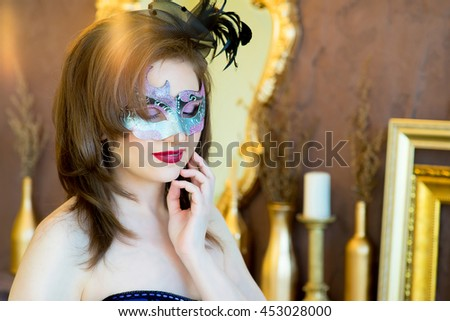 woman with black curly hair and a masquerade mask posing on a brown background - stock photo