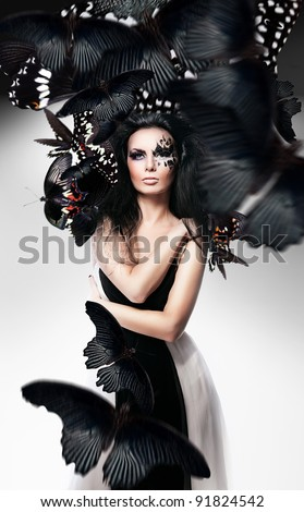 Woman with black hair and art make up and black butterflies - stock photo