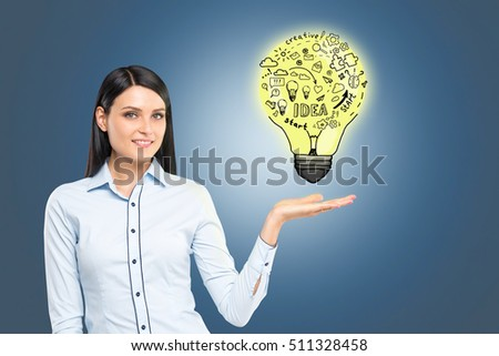 Woman with black hair is holding a light bulb business idea sketch white standing near dark blue wall.