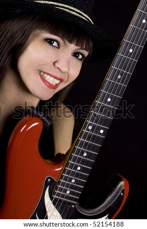 Woman with black hat playing country music on guitar