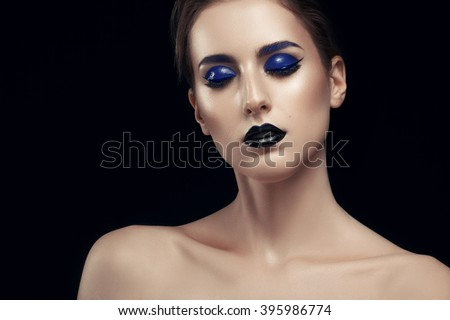 Woman with black lips and blue make up on black background in studio