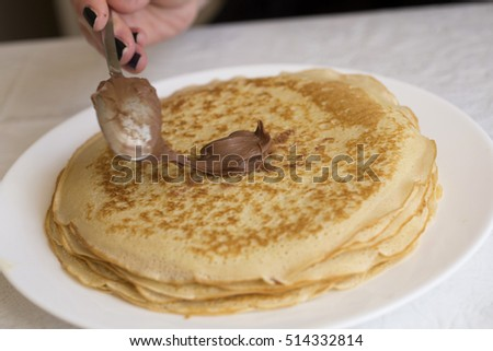 Woman with black nails dab pancakes with chocolate