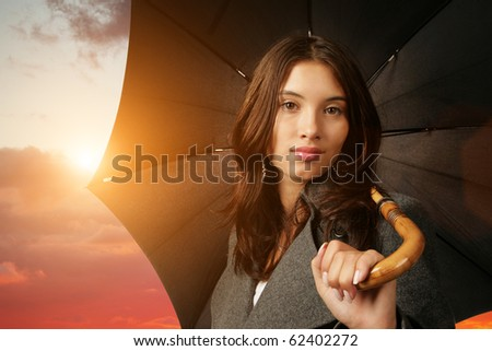 Woman with black umbrella over scenic sunset sky background.