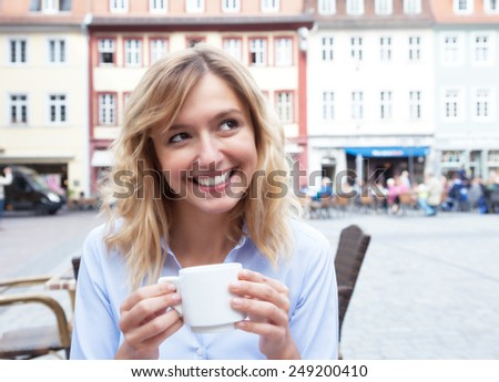 Woman with blond hair drinking a coffee and looking around - stock photo