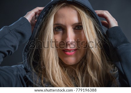 Woman with blonde hair and blue eyes dressed in dark color and with her head covered, she poses in a photographic studio with black background.