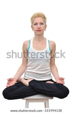 Woman with blonde short haircut sitting in lotus position on a stool