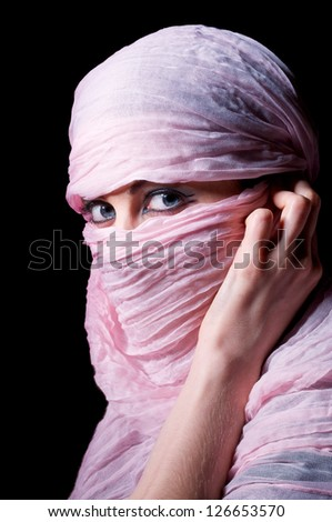 woman with blue eyes in pink hijab looks in camera - stock photo