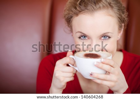 woman with blue eyes looking over cup of cappuccino in caf�© - stock photo