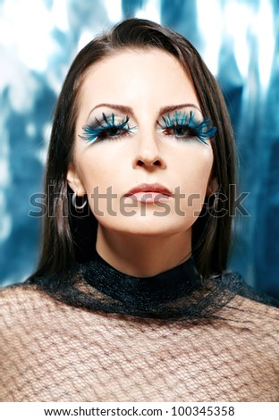 Woman with blue feather lashes. Fashion photo