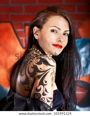 Woman with body art against graffiti brick wall.