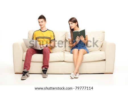 woman with book peaking at boyfriend with laptop - stock photo