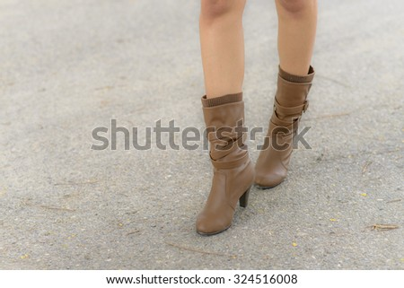 Woman with boot waiting on the asphalt road; Low angle shoot - stock photo