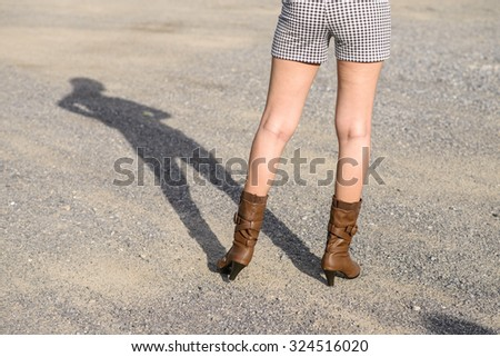 Woman with boot waiting on the road; Shadow shown; Low angle shoot - stock photo