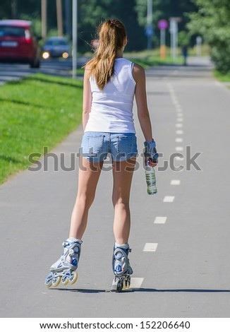 Woman with bottle of water ride rollerblades in the park. Back view. - stock photo