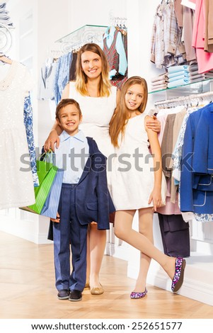 Woman with boy and girl stand close while shopping