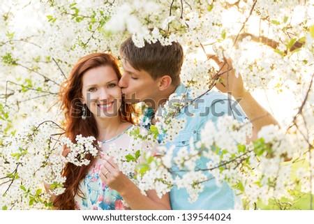 woman with boyfriend in spring flower garden - stock photo