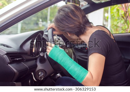 woman with broken hand in cast sitting in car, insurance concept