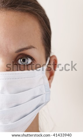woman with brown hair and a medical mask for protection again influenza. Shallow depth of field. Copy space for your text.