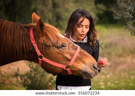 Woman with brown hair gives a radish to his horse
