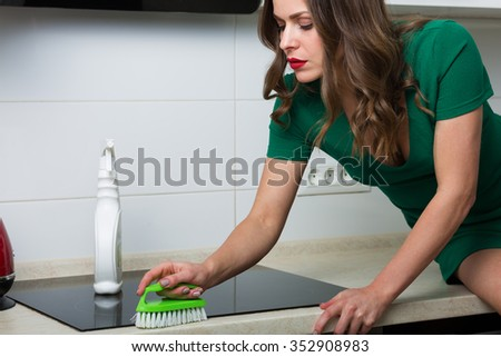 Woman with brush and cleaning spray cleaning up her kitchen