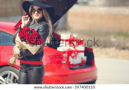 woman with bunch of red flowers near red car full of gift boxes. roses, woman and car. car trunk full of presents. happy woman. holiday. Sexy woman with bouquet. Happy woman near luxury red car - stock photo