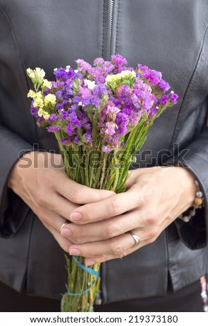 woman with bunch of wild flowers, close up - stock photo