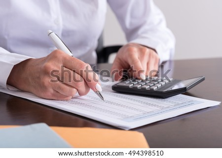 Woman with calculator doing her accounting