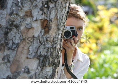 Woman with camera hiding behind the tree