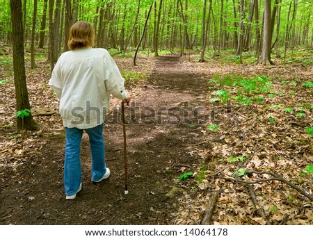 Woman with cane walking in the woods - stock photo