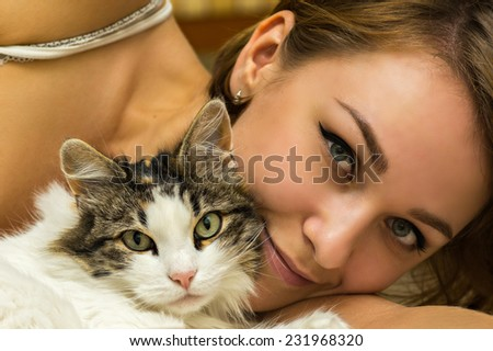 woman with cat on bed - stock photo