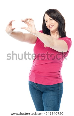 Woman with cell phone taking picture of herself - stock photo
