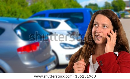 woman with cellphone in front of cars