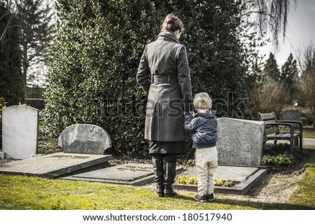 Woman with child at graveyard - stock photo