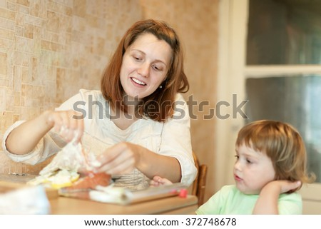 Woman with child cooks in the kitchen together