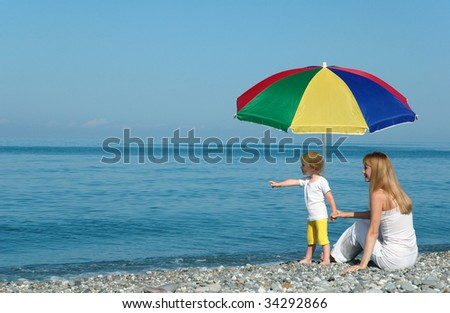 Woman with child under umbrella on the beach - stock photo