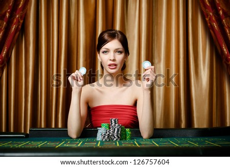 Woman with chips sitting at the roulette table at the gambling house - stock photo