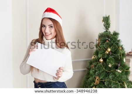 Woman with Christmas hat holding blank banner - stock photo