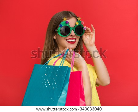 Woman with Christmas party glasses and shopping bags - stock photo