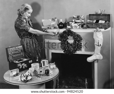 Woman with Christmas presents on mantle - stock photo