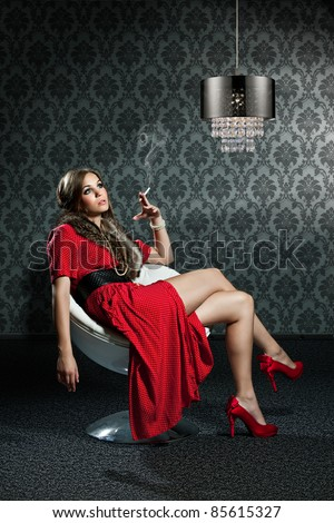 woman with cigarette and red dress is sitting in front of a sixties wallpaper - stock photo