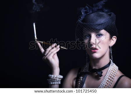 Woman with cigarette and vintage hat with long legs against dark background - stock photo