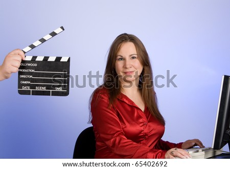 Woman with clapperboard in forground of image. - stock photo