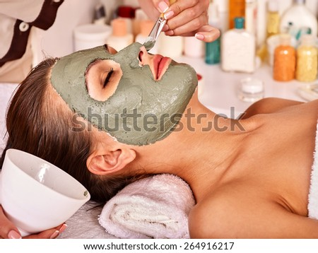 Woman with clay facial mask in beauty spa. Close up.