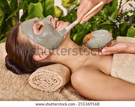 Woman with clay facial mask in beauty spa. In background tropical plants - stock photo