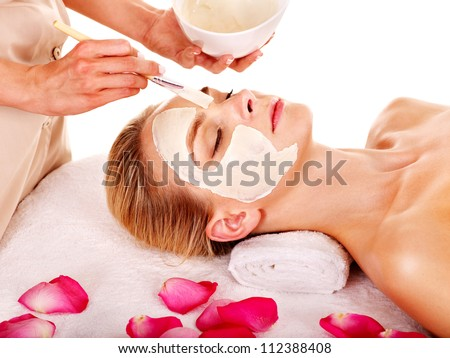 Woman with clay facial mask with rose petal. Isolated. - stock photo