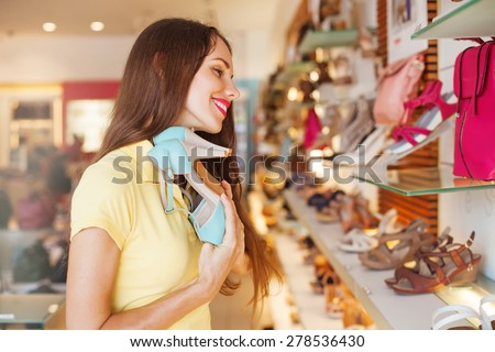 woman with closed eyes and great pleasure holding the best shoes in a shop - stock photo