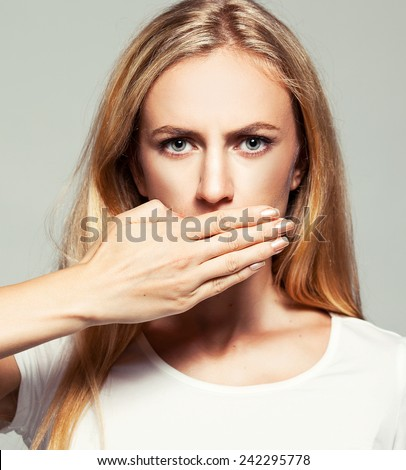 Woman with closed mouth. Female covers her mouth with her hands. Silence, fear, violence. - stock photo